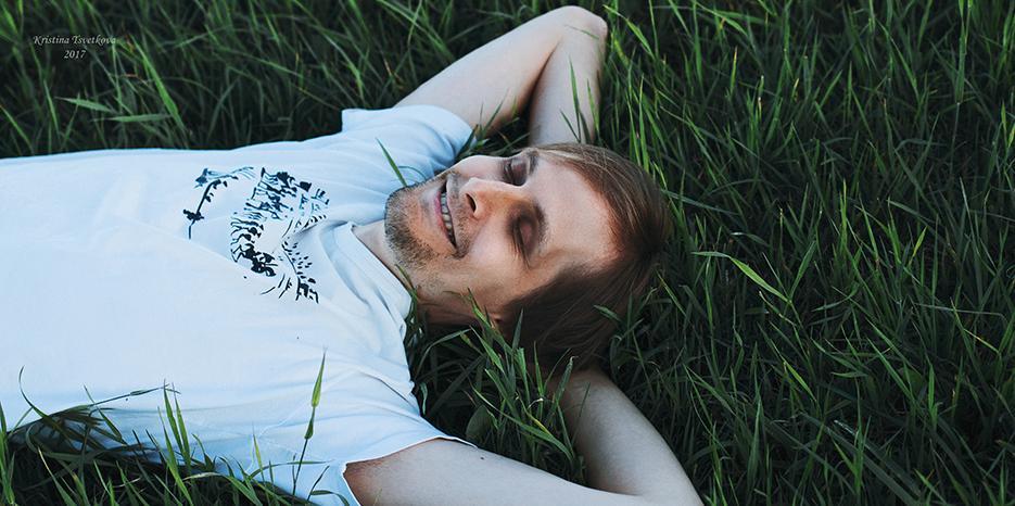 Timo Kuusiola lekottelee hymyillen selällään nurmikolla.