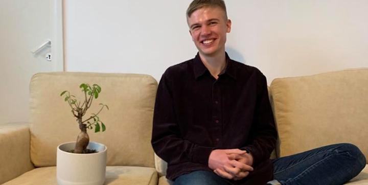 Lyhythiuksinen ja tummiinpukeutunut Jyry Virtanen istuu rennosti ja nauraen beessin värisellä sohvalla vieressään huonekasvi.