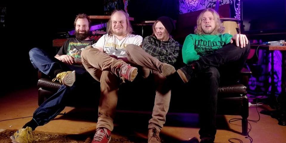 FUCK-USHIM-bändin neljä jäsentä istuvat rinnakkain pienellä sohvalla musiikkiklubiympäristössä.