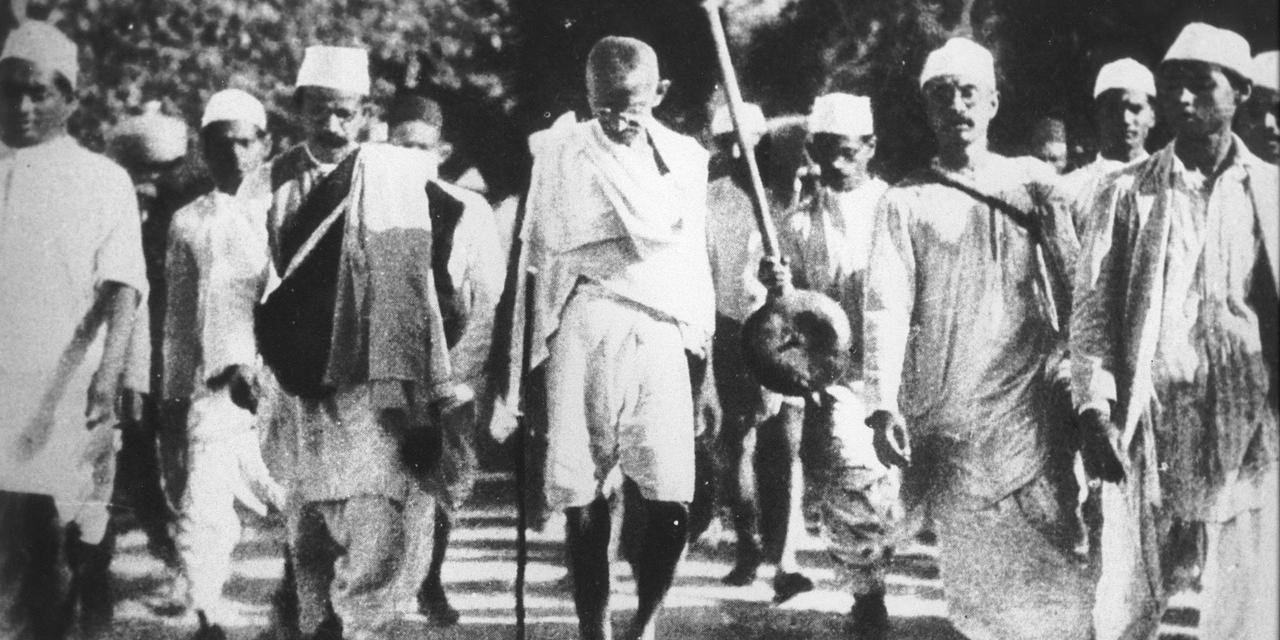Mahathma Gandhi kävelee ihmisjoukon keskellä