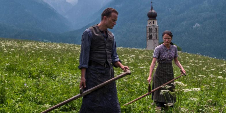 Hidden Life -elokuvan hahmot kulkevat niityllä maatyövälineet käsissään.