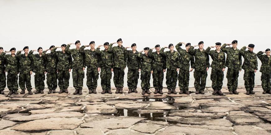 Valokuva Kesälomana sotilasleiri -sarjasta. Joukko teini-ikäisiä seisoo kalliolla rivissä maastoasuissa ja tekee kameralle sotilastervehdyksen.