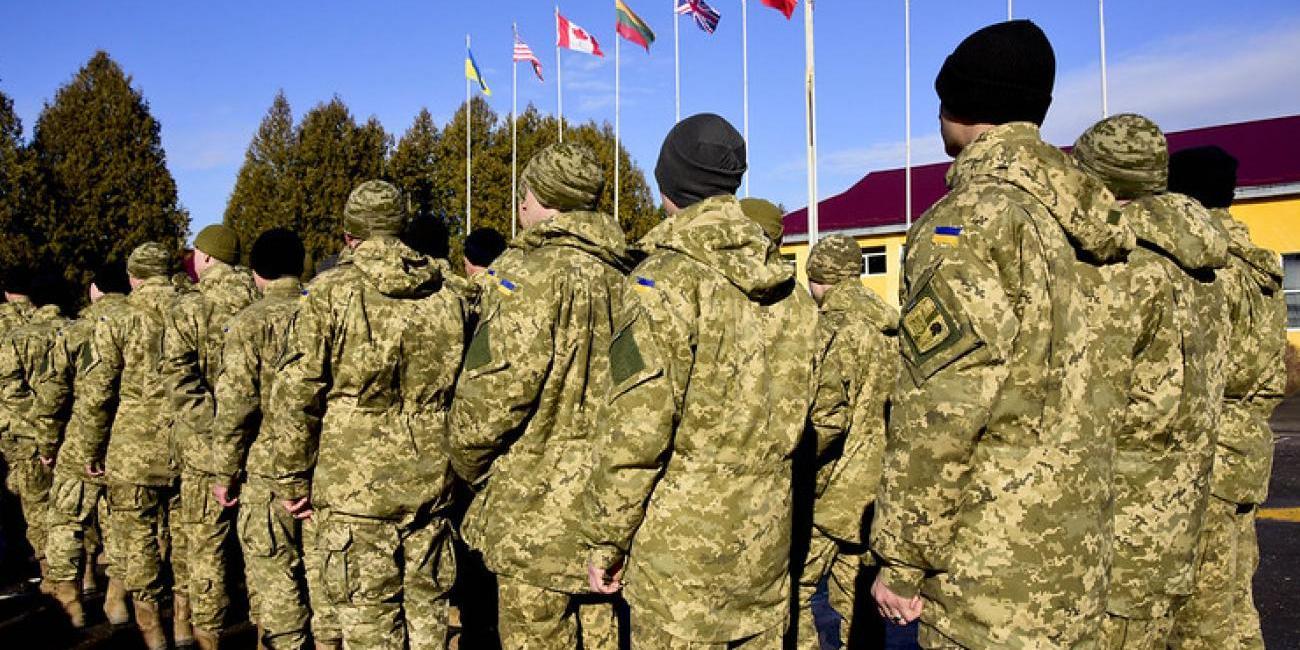 Ukrainalaisia sotilaita rivissä, lippuja liehuu takana.