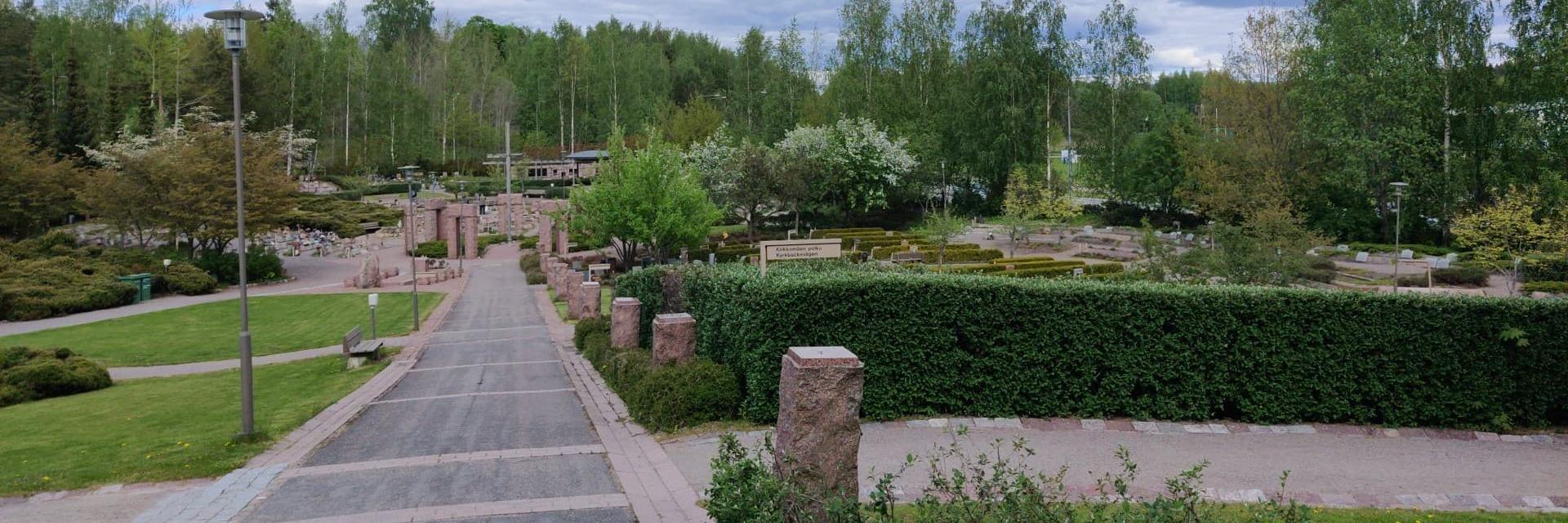 Puolipilvinen päivä hautausmaalla. Tie jonka päässä on suuri risti, suorat rivit joissa on eri muotoisia hautakiviä, pensasaita etualalla.