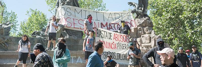 Mielenosoittajat ovat kokoontuneet suurten banderollien kanssa patsaan ympärille.