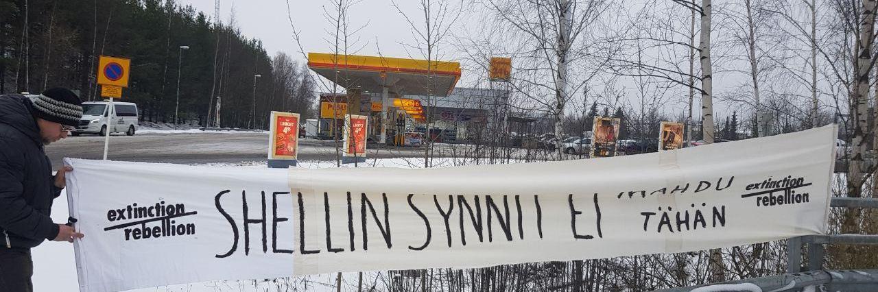 """Kuvassa näkyy Shellin huoltoasema Tampereella. Etualalla Elokapinan logoilla varustettu banderolli, jossa lukee: """"Shellin synnit ei mahdu tähän"""""""