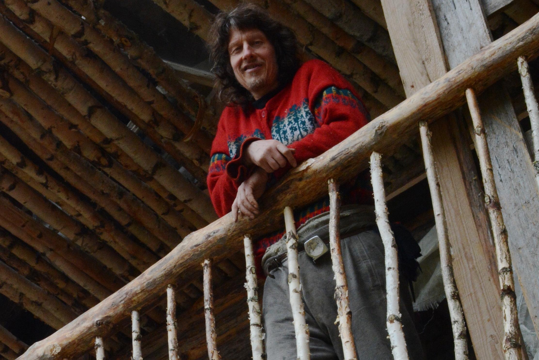 Lasse Nordlund seisoo hirsirakennuksen terassilla punaisessa villapaidassa ja katsoo kameraa.