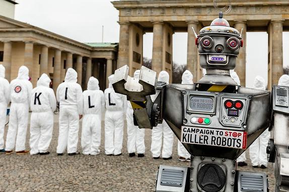Tappajarobotiksi pukeutunut hahmo seisoo etualalla kasvot kameraan päin. Taustalla selin kääntyneitä, valkeisiin vaatteisiin pukeutuneita mielenosoittajia.