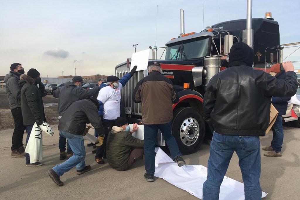 Joukko paksuihin vaatteisiin pukeutuneita mielenosoittajia seisoo ja istuu aseita kuljettavan trukin edessä.