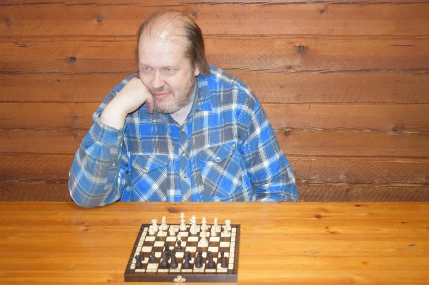 Kaj Raninen istuu pöydän ääressä hirsiseinäisessä huoneessa nojaten käteensä. Hänen edessään on shakkilauta.
