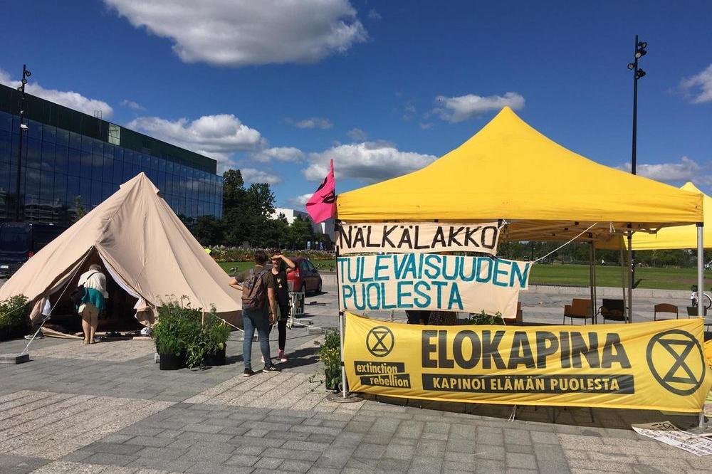 """Helsingin kansalaistorille pystytetyssä keltaisessa teltassa on banderolleissa tekstit: """"Nälkälakko tulevaisuuden puolesta"""" ja """"Elokapina - Kapinoi elämän puolesta""""."""