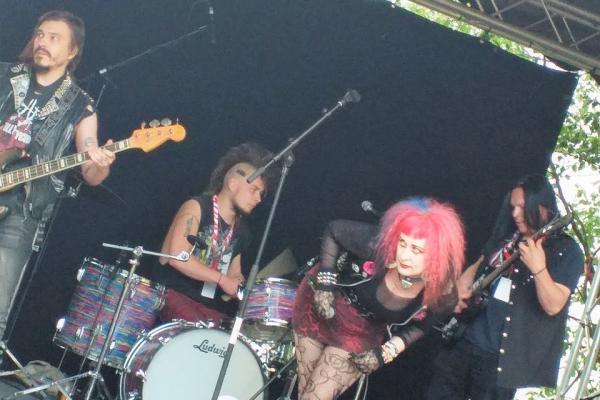 Anthrax Fields -punkbändi keikalla. Laulaja Magentalla on pörröiset vaaleanpunaiset hiukset.