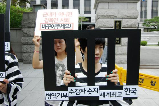 Eteläkorealainen aseistakieltäytyjä pitää kiinni pahvistista tekokaltereista ja on pukeutunut musta-valko-raidallisiin vanginvaatteisiin.
