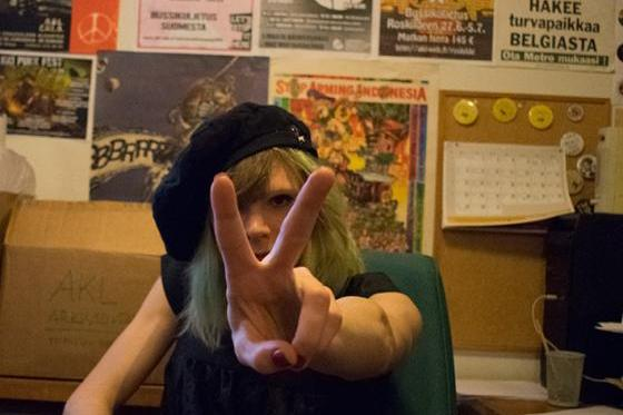 Valokuva. Mustiin pukeutunut baskeripäinen totaalikieltäytyjä Elsa Tauria näyttää voitonmerkkiä. Taustalla seinällä on aseistakieltäytymiseen liittyviä uutisia ja julisteita.