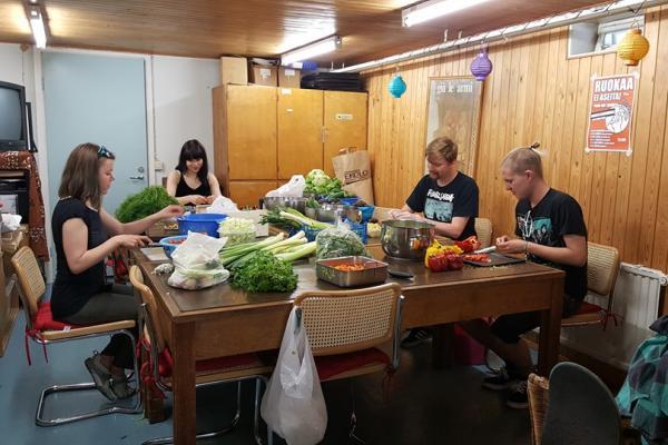 Neljä nuorta vapaaehtoista istuu pöydän ääressä pilkkomassa vihanneksia.