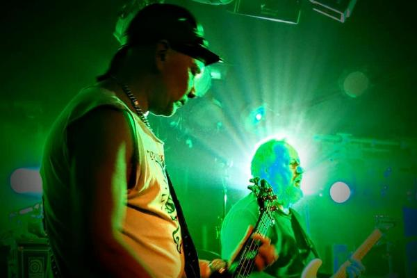 """Vihreä valo loistaa Arto """"Otra"""" Jehkisen kasvojen takaa. Tuomas """"Tumppi"""" Moilanen soittaa kuvassa etualalla."""