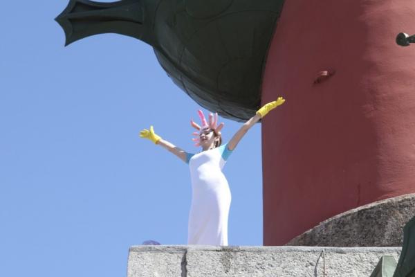 Venäläinen taiteilija Elizaveta Savolainen seisoo kädet levällään valkoisiin pukeutuneena kiivenneenä rostraalimonumenttiin antimilitaristisessa performanssissa..