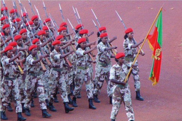 Joukko naissotilaita marssii maastopuvuissa ja aseet olalla. Etummainen kantaa Eritrean puna-vihreää lippua.
