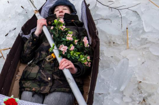 Talvitakkiin ja pipoon pukeutunut ihminen makaa silmät suljettuna ruumisarkussa pitäen molemmilla käsillään kiinni airosta. Hänen rinnalleen ja jalkojensa päälle on laskettu kukkia. Ruumisarkun ympärillä on lunta.