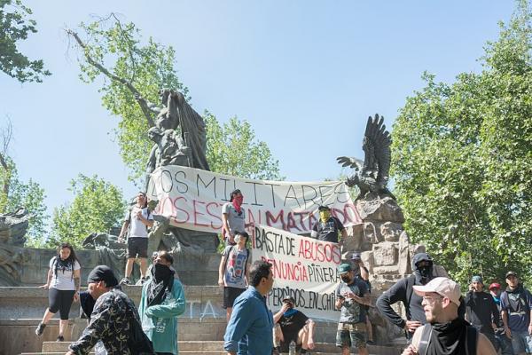 Kuva Chilessä tapahtuvasta mielenosoituksesta patsaiden edessä.