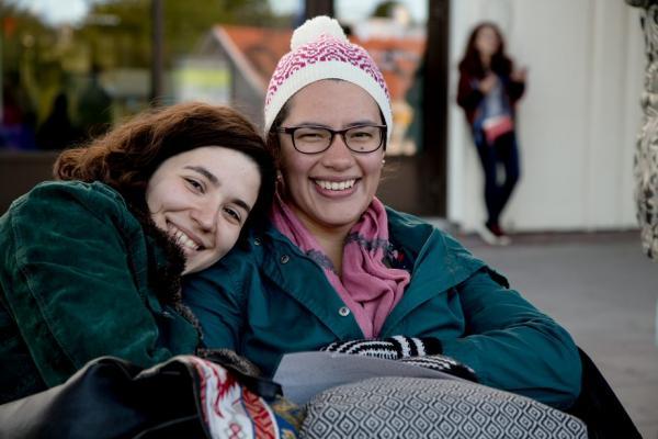 Valokuva. Kaksi nuorta on pukeutunut lämpimiin vaatteisiin ja katsoo nauraen kameraa. Vasemmalla istuva  on laskenut päänsä oikealla istuvan olalle.