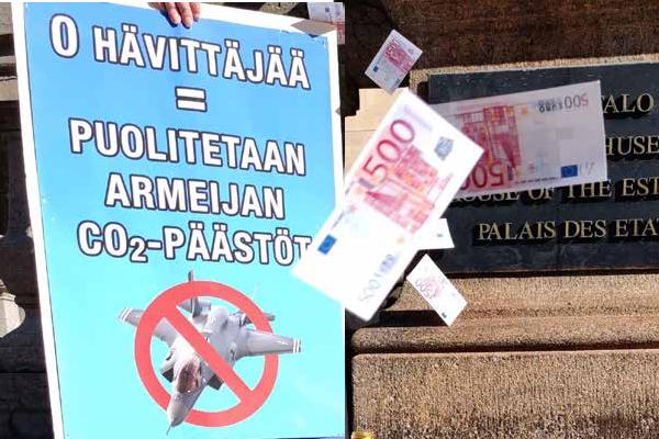 Putoavia seteleitä hävittäjähankintoja vastustavan kyltin edessä.