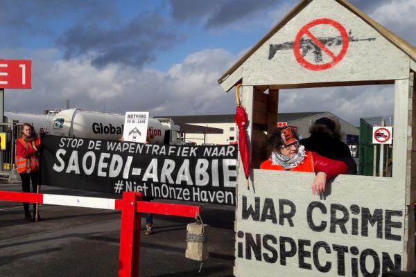 Kaksi ihmistä seisoo huomioliiveissä kojussa, jossa lukee War Crime Inspection. Takana näkyy banderolli flaaminkielisellä tekstillä: Stop de wapentrafiek naar Saoedi-Arabie