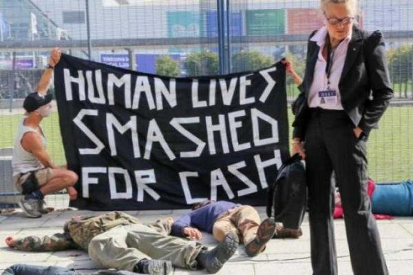 Maassa makaa levällään ihmisiä, jotka esittävät kuolleita. Etualalla pukuun pukeutunut mies katselee kohti kameraa silmälasiensa yli. Takana aktivistit pitävät banderollia: Human lives smashed for cash.