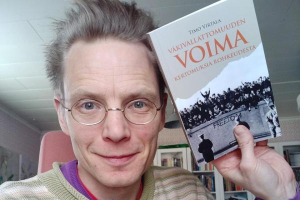 Timo Virtala nostaa kädellään kirjansa Väkivallattomuuden voima kasvojensa viereen.