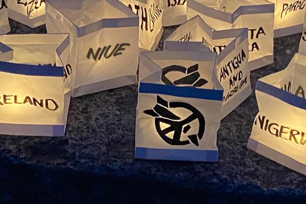 Paperilyhtyiin on kirjoitettu ydinasekieltosopimuksen ratifioineiden valtioiden nimiä ja ICAN-kampanjan logona, jotka esittävät kieltomerkkiä tyylitellyn ydinohjuksen päällä.