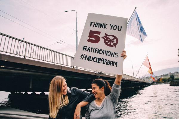 """Kaksi hymyilevää ihmist pitää kylttiä: """"Thank you 50 ratification #NuclearBan"""""""