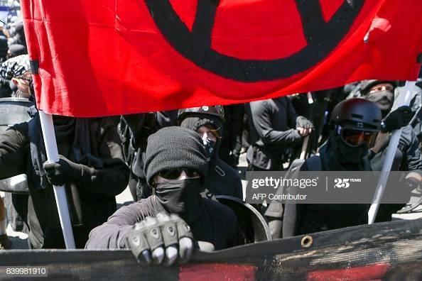 Mustiin pukeutuneet ja huivein, kilvin ja kypärin varustautuneet mielenosoittajat kantavat banderolleja ja punamustaa anarkistilippua.