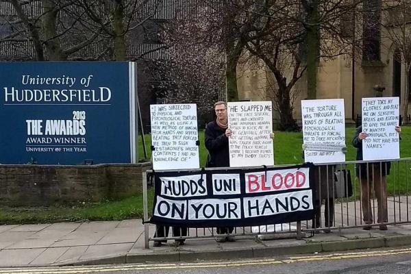 Mielenosoitus Hudderfieldin yliopiston edustalla. Mielenosoittajat kantavat pieniä kylttejä, joissa on sitaatteja vankien omista kokemuksista Bahrainin poliisivoimien käsissä, sekä suurempaa banderollia, jossa on teksti Hudds Uni Blood on Your Hands.
