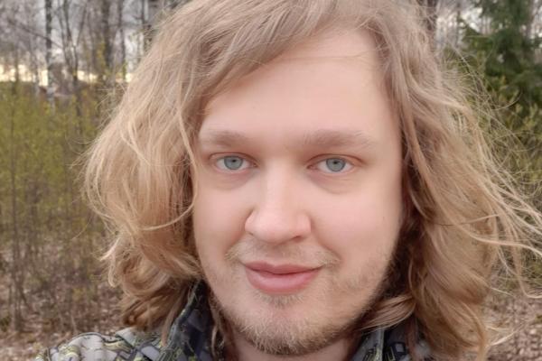 Oliver Ojalla on pitkät vaaleat hiukset auki. Hän hymyilee kameralle.