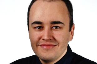 Mustaan takkiin pukeutunut Bülent Sahin katsoo kameraan hymyillen.