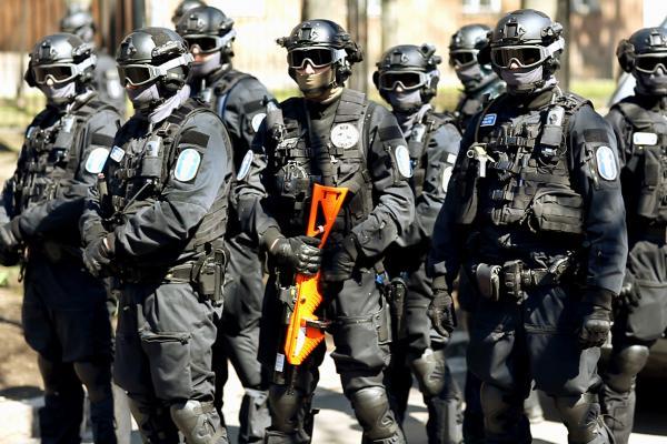 Still-kuva Annika Rauhalan Jouha-videoteoksesta. Kokokuva voimakkaasti varustautuneesta ja kasvonsa peittäneestä Poliisin joukkojenhallintaryhmästä.